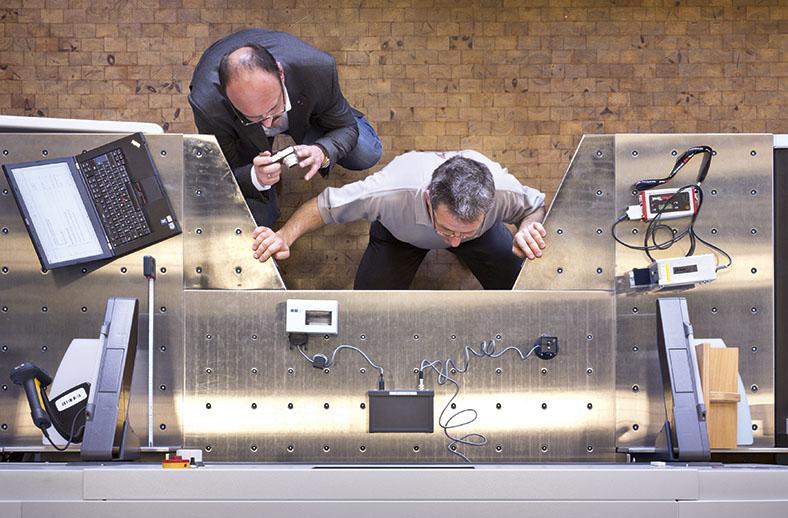 Aus der Vogelperspektive sieht man auf zwei Männer herunter, die in der Hocke vor einer Maschine mit Metallgehäuse sitzen und hineinschauen. Beide tragen eine Brille. Einer der Männer hält eine kleine Kamera und macht Bilder. Links auf der Maschine liegt ein aufgeklapptes Notebook, oben auf der Maschine ist ein Messgerät mit Kabeln angebracht.