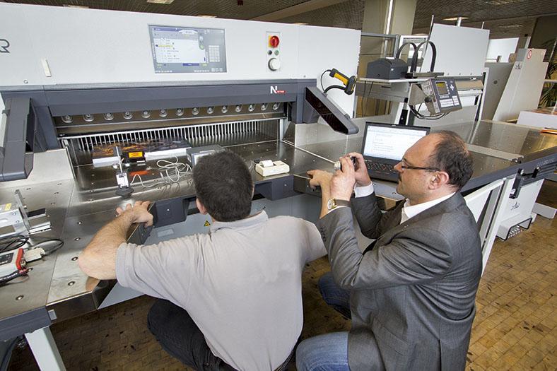 Die Abbildung zeigt zwei Männer in der Hocke vor einer Maschine sitzen. Der Mann links im grauen Hemd ist von hinten zu sehen, er begutachet das Innere der Maschine an, während der Mann rechts in grauem Sakko im Profil zu sehen ist, Er trägt eine Brille und macht Bilder mit einer kleinen Kamera. Hinter dem Mann liegt ein aufgeklapptes Notebook auf der Maschine.