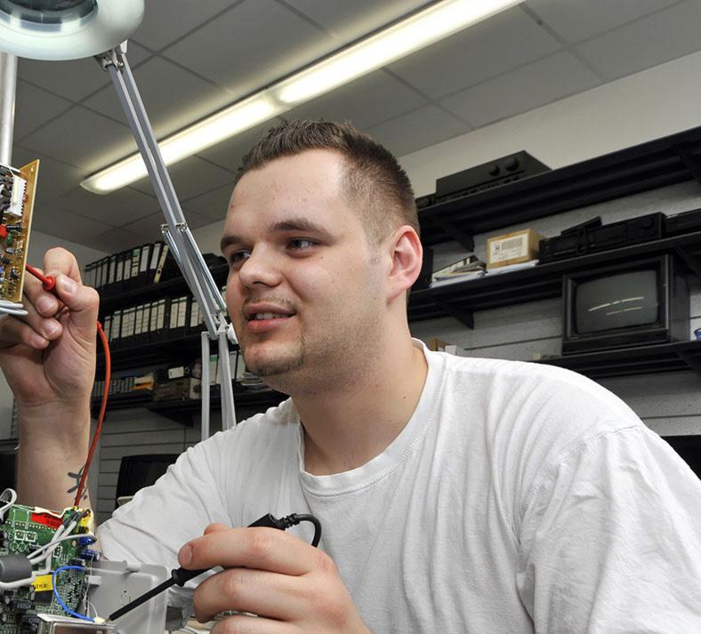 Elektrische Gefährdung: Prüfingenieur in einem Elektrolabor macht einen Funktionstest an einer Platine.
