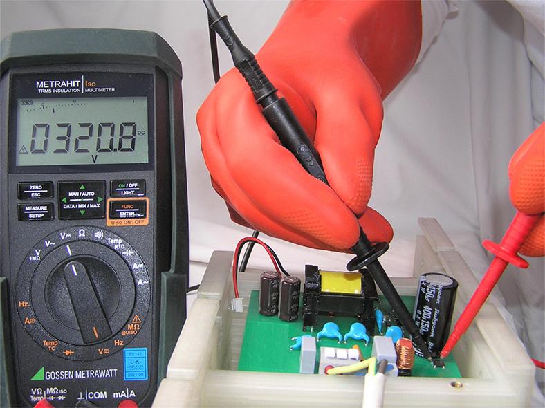 Elektrische Gefährdungen: Messen der Kondensatorspannung an einem unter Spannung stehenden Bauteil, links daneben Messgerät mit Spannungsanzeige.