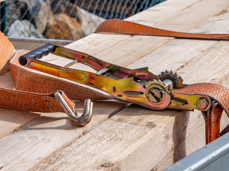 Ladungssicherung: Spanngurt liegt über Holzbalken.