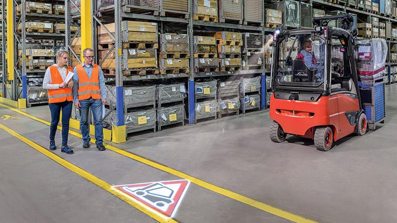 Gabelstapler Gruppe von zwei Personen in einem Warenlager, am Boden ein LED-Warnsymbol.