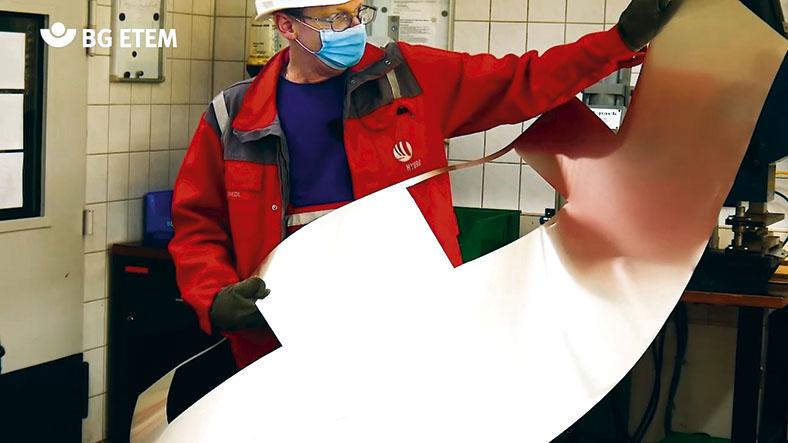 Peter Friedl in Persönlicher Schutzausrüstung mit Helm und Mundschutz hält ein Aluminiummuster mit speziellen, schnittfesten Handschuhen.Peter Friedl in Persönlicher Schutzausrüstung mit Helm und Mundschutz hält ein Aluminiummuster mit speziellen, schnittfesten Handschuhen.