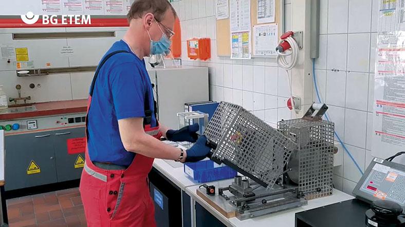 Peter Friedl hebt mit behandschuhten Händen ein Schutzgitter hoch, das beim Anheben die Maschine stoppt.