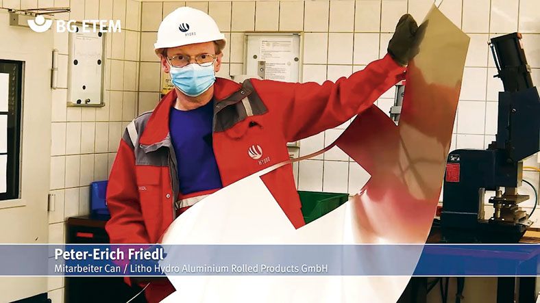 Peter Friedl in Persönlicher Schutzausrüstung mit Helm und Mundschutz hält ein Aluminiummuster mit speziellen, schnittfesten Handschuhen.