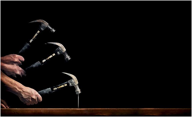 Lichtflimmern und Stroboskopfeffekt: Hammer schlägt auf einen Nagel vor schwarzem Hintergrund, man sieht den bewegten Hammer in mehreren Positionen.