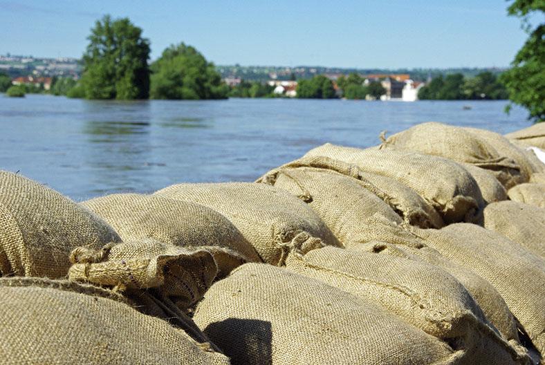 Flutkatastrophe: Sandsäcke an Ufer eines Gewässers.