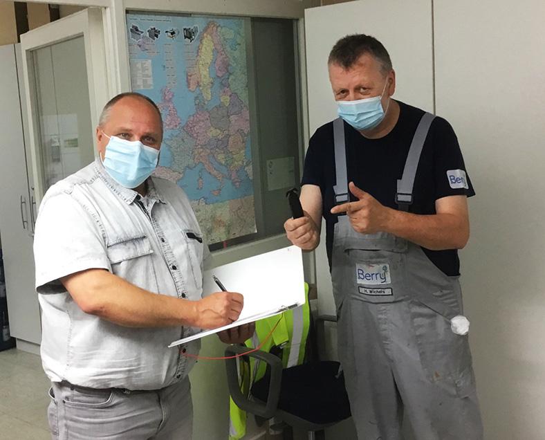 Schnittverletzungen: Zwei Männer mit Mundschutz stehen in zusammen, einer schreibt in einen Ordner, der andere hält ein Sicherheitsmesser.