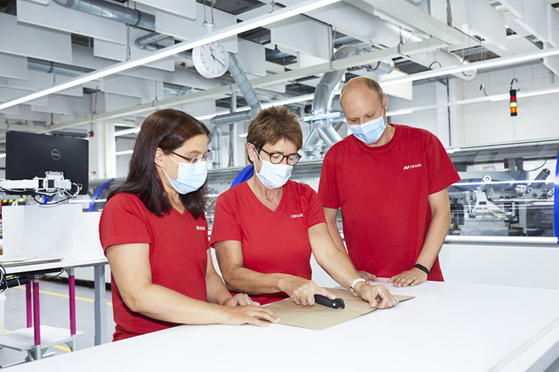 Schnittverletzungen: Drei Personen in roten T-Shirts mit FFP2-Maske bei Teambesprechung zum Einsatz von Sicherheitsmessern in Fabrikhalle.