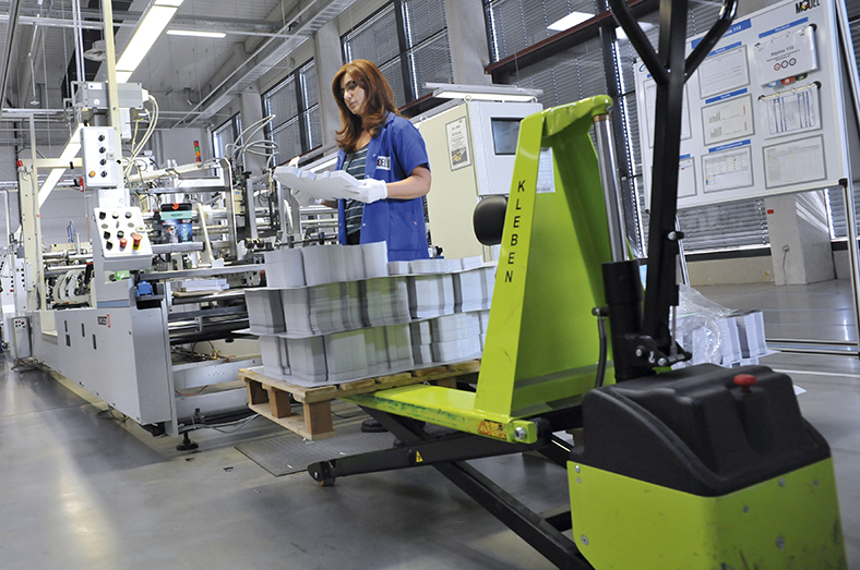 Das Foto zeigt eine Facharbeiterin vor aufgestapeltem Papier. Eine Packung von fertig gedrucktem hält die Frau mit beiden Händen fest.