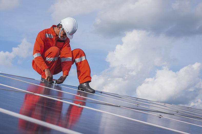 Dieses Bild zeigt einen Arbeiter mit weißem Schutzhelm und orangefarbenen Overall. Er sitzt in der Hocke auf einer Solaranlage und überprüft etwas.