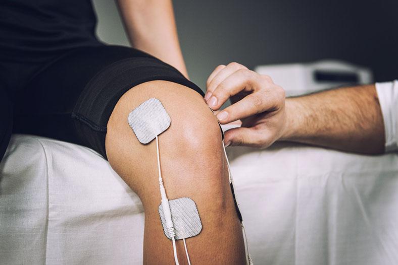 Das Bild zeigt ein Knie während einer Elektrotherapie. Das Knie ist mit Pads und Kabeln verklebt.