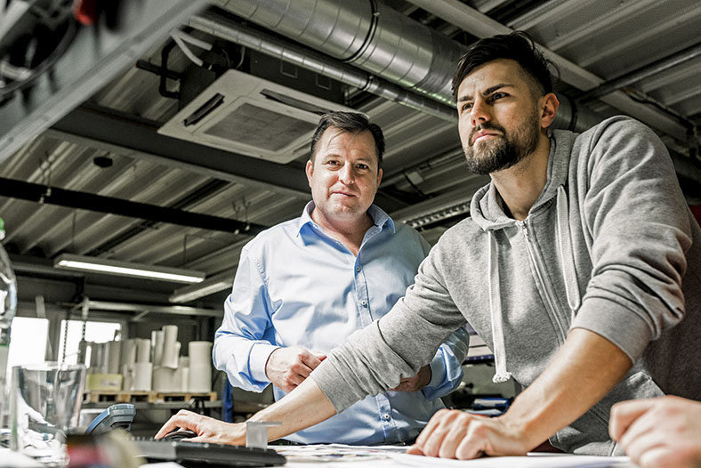 Das Foto zeigt den Chef und einen Beschäftigten während des Workshops an einem Arbeitsplatz.
