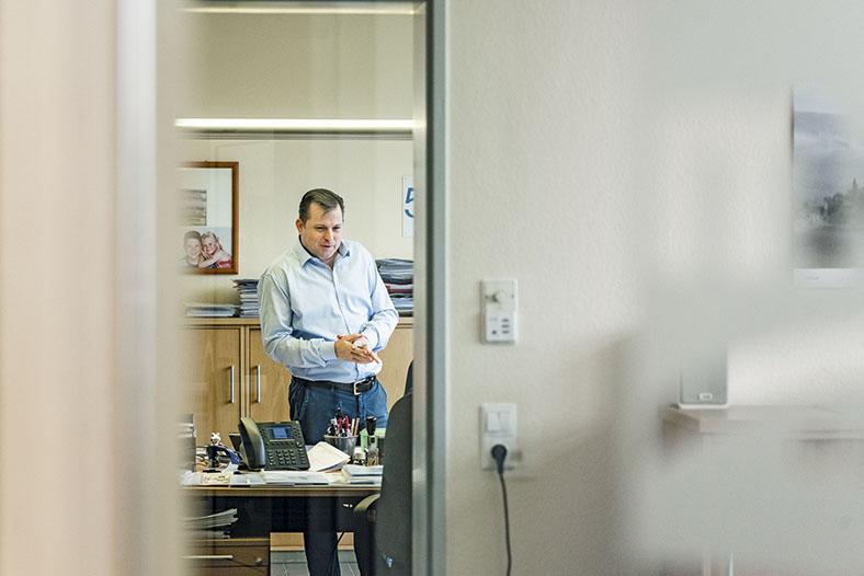 Dieses Foto zeigt einen Mann in der Entfernung der vor einem Schreibtisch steht. Man erkennt Schreibutensilien und ein Tischtelefon. Im Vordergrund eine geöffnete Tür.