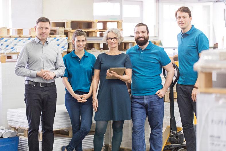 Das Foto zeigt die Geschäftsführung und Beschäftigte alle in einer Reihe stehend. Die Beschäftigten tragen alle Tshirts inderselben Farbe. Die Chefin hält eine Unterlage in der Hand.