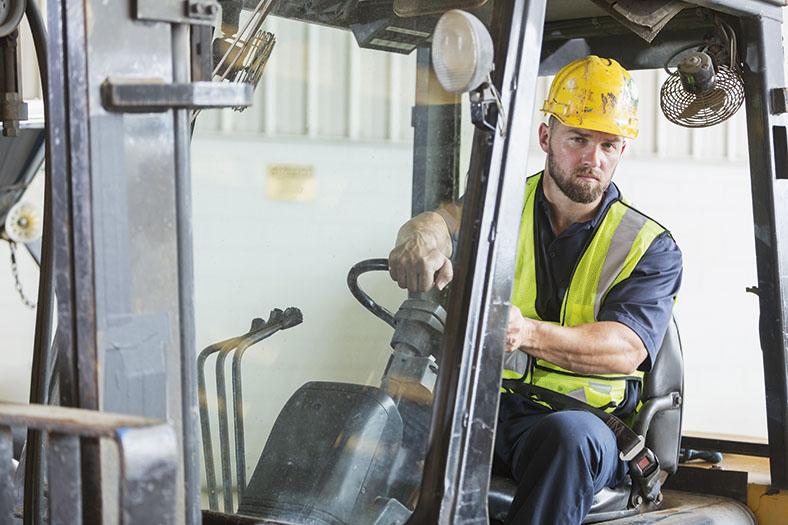 Ein Arbeiter mit Schutzhelm und Schutzweste sitzt in einem Gabelstabler.