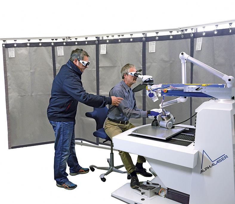 Dieses Bild zeigt einen Mann, der mit Schutzbrille an einem Tisch sitzt auf dem ein Lasergerät steht. Er schaut sich etwas an.Seine rechte Hand steckt in einer Schutzvorrichtung. Ein anderer Mann steht neben ihm und zeigt mit seiner rechten Hand inRichtung Lasergerät.