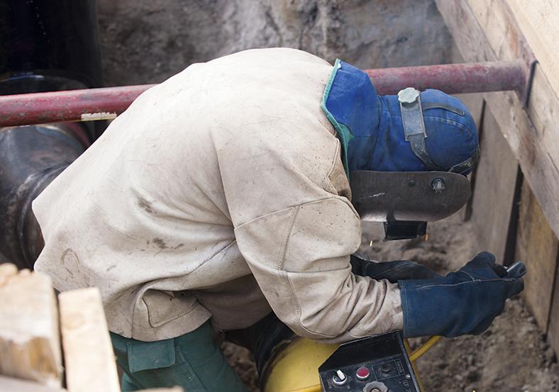 Das Foto zeigt einen Arbeiter mit Schutzmaske- und Brille und Schutzhandschuhen. Er kniet in einem ausgebaggerten Erdloch. Mit der rechten Hand bedient er einen Hebel.