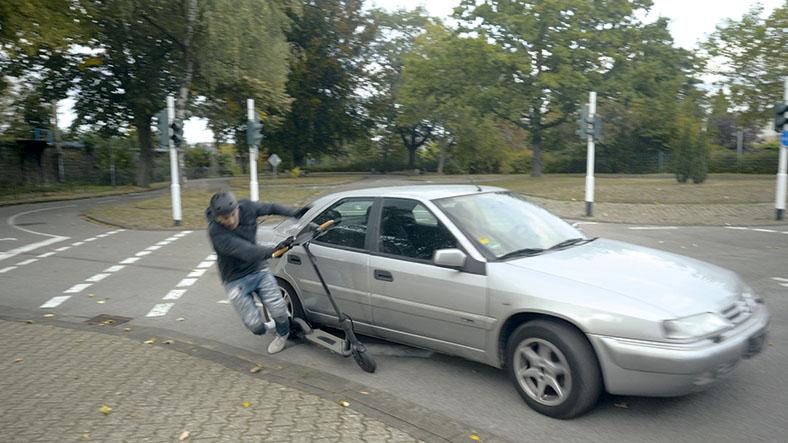 Auf diesem Foto ist ein silberfarbener PKW zu sehen, der einen Jungen mit einem E-Scooter rammt.