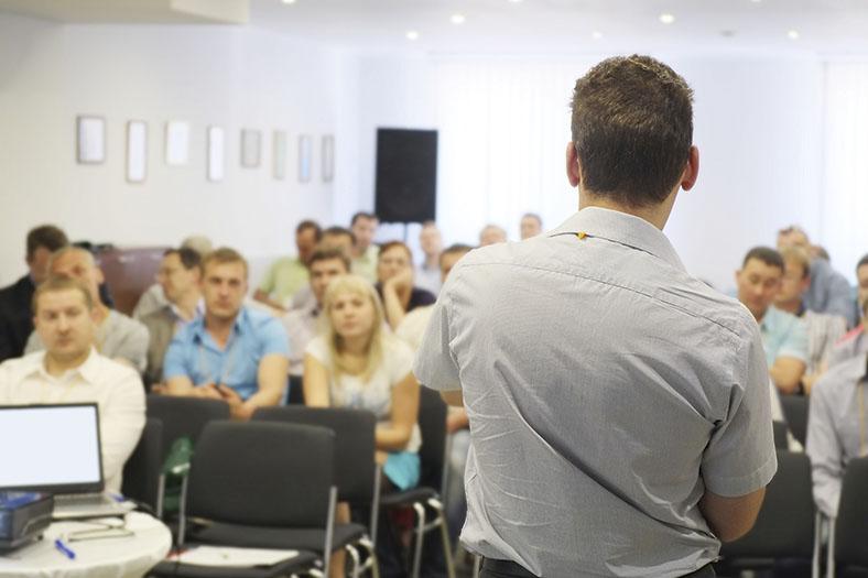 Auf diesem Foto sind einige Personen zu erkennen, während eines Seminars. Der Seminarleiter steht mit dem Rücken inRichtung des Betrachters.