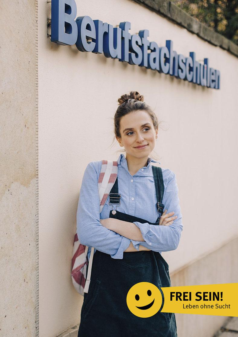"""Das Foto zeigt eine junge Frau mit verschränkten Armen. Sie hat eine Tasche umhängen. Im Hintergrund ist eine Mauer. Darauf steht Berufsfachschulen. Im Foto unten ist ein gelbes Logo mit Smiley und dem Text """"Frei sein!"""" abgebildet."""