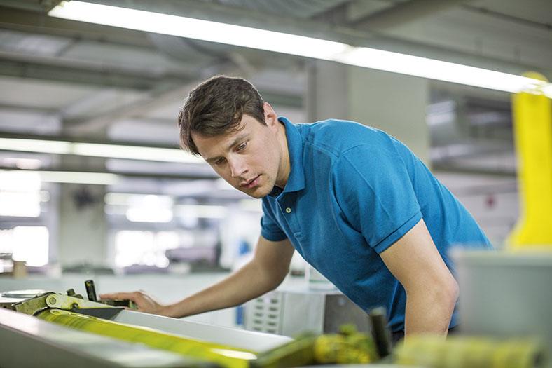Das Bild zeigt einen Mann, der an einer Druckmaschine etwas nachschaut.