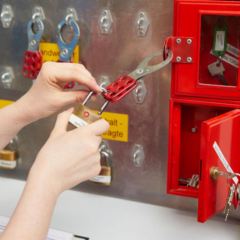 Wegschließen des Schlüssels: Im nächsten Schritt wird der Schlüssel für die beiden gleichschließenden Schlösser, die nun fest an der Maschine hängen, in einen der drei Glaskästen gehängt.