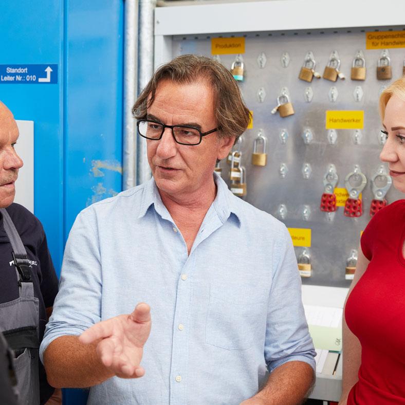Anton Forner (Mitte), interne Fachkraft für Arbeitssicherheit, schult Freischaltbeauftragte direkt am Schlüsselbord.