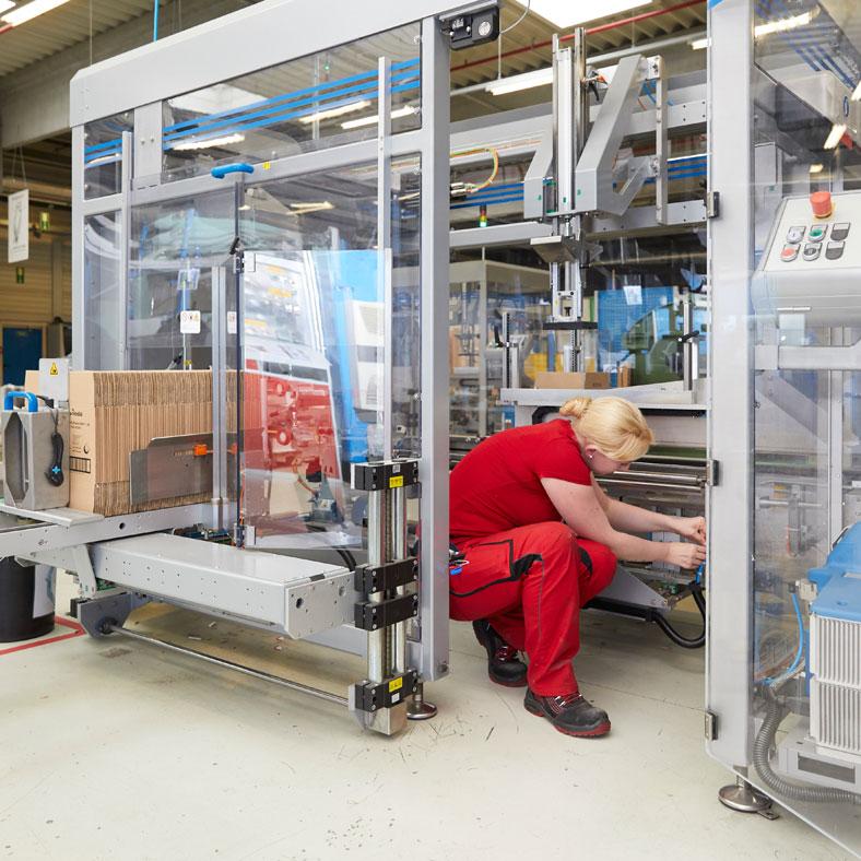 Instandhaltungsarbeiten innerhalb einer Verpackungsanlage bei FHP Augsburg. Rechts im Bild ist die geöffnete trennende Schutzeinrichtung sichtbar: Eine Türe mit Schutzschalter mit Personenschutzfunktion als Zutrittsverhinderung während des Betriebs.