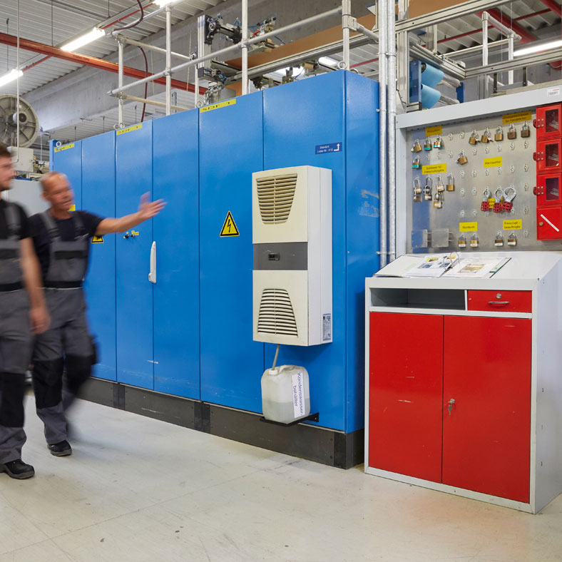 Das Bild zeigt zwei Facharbeiter, die an einer großen Maschine entlang laufen. Einer der Facharbeiter hält seine linke Hand inRichtung Maschine und erklärt dem Kollegen etwas.