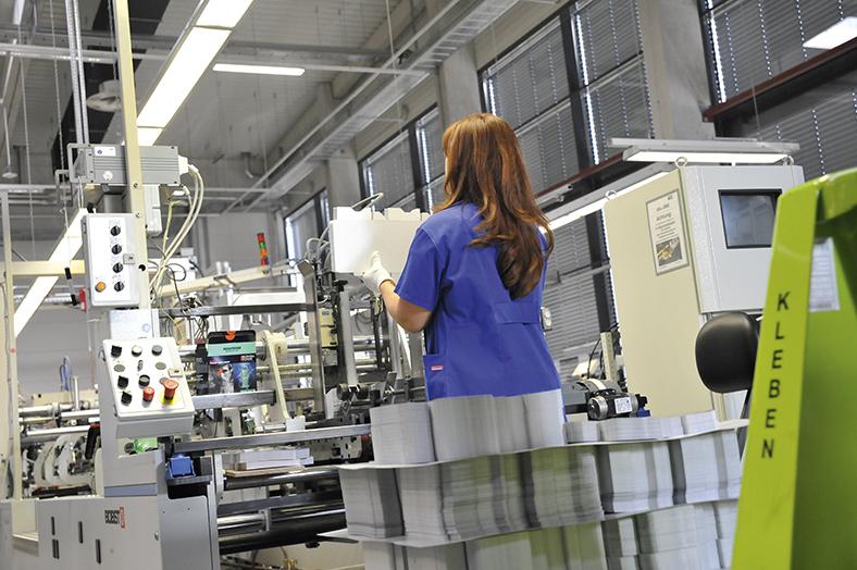 Das Foto zeigt eine Frau an ihrem Arbeitsplatz in der Weiterverarbeitung von Papier an einer großen Maschine.