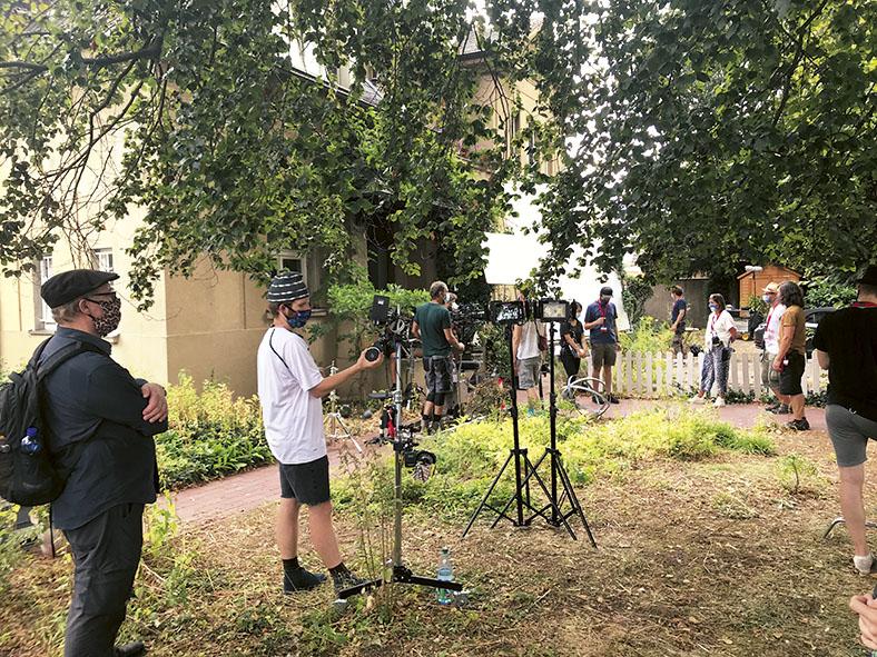 Mitarbeiter eines Filmteams stehen in einem Garten mit weißem niedrigem Lattenzaun. Einige Personen tragen einen Mund-Nasen-Schutz. Im Vordergrund arbeitet ein Mitglied an einem Ständer mit mehreren Fotoapparaten, daneben stehen zwei Ständer mit Lampen.
