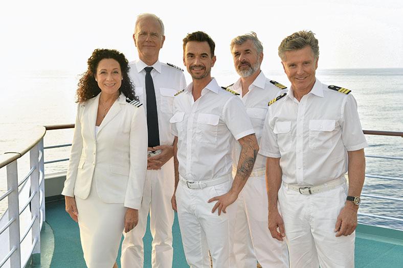 Gruppenfoto der 5-köpfigen Filmcrew des Traumschiffs, von links nach rechts stehen eine Frau mit dunklen lockigen Haaren in einem weißen Marineblazer und vier Männer in kurzärmeligen weißen Marinehemden mit gestreiften Schulterklappen. Im Hintergrund sieht man die Schiffsreling und das Meer.