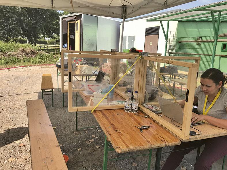 Das Foto zeigt am rechten Bildrand eine Frau, die im Freien an zwei zusammengestellten Biertischen sitzt und an einem Notebook arbeitet. Auf den Biertischen sind Holzrahmen mit Glaseinsätzen als Trennwände aufgestellt. Im Hintergrund sieht man ein Gebäude mit weißen und grünen Wänden. Zur Person