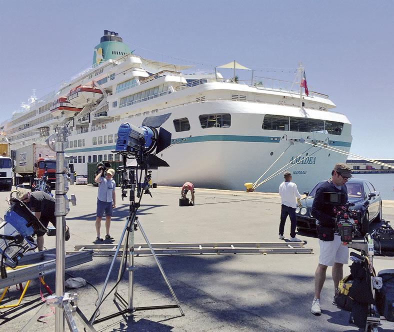 Hafenszene in der Sonne: Das Foto zeigt ein Kreuzfahrtschiff in weiß mit türkisfarbenen Elementen an einer Mole vertäut. Im Vordergrund sieht man mehrere Mitarbeiter eines Filmteams beim Auf- oder Abbau von Filmausrüstung, links am Bildrand stehen zwei LKWs.