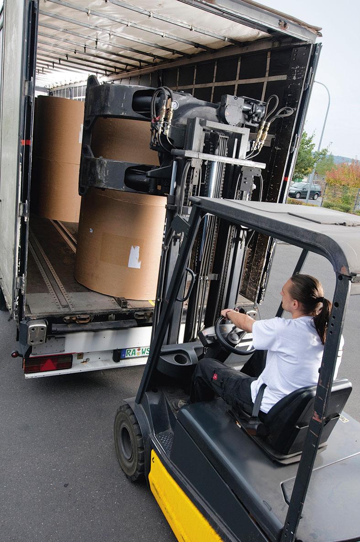 Ein Gabelstapler mit Greifarmen entlädt große, braun verpackte Rollen aus dem Laderaum eines LKWs. Der Fahrer trägt ein weißes Hemd mit kurzen Ärmeln und hat hellbraune, lange Haare, die zu einem Pferdeschwanz zusammengebunden sind.