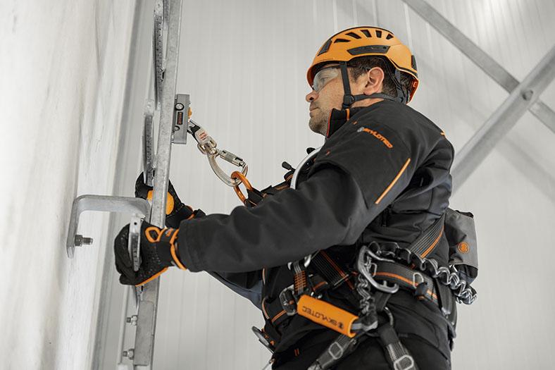 Mann in persönlicher Schutzausrüstung in schwarz und orange mit orangenem Helm und Sicherheitsbrille hält sich mit behandschuhten Händen an einer vertikalen Leiter fest, er trägt ein Gurtsystem am Oberkörper und ist mit einem Steigschutzläufer an einer Schiene gesichert.