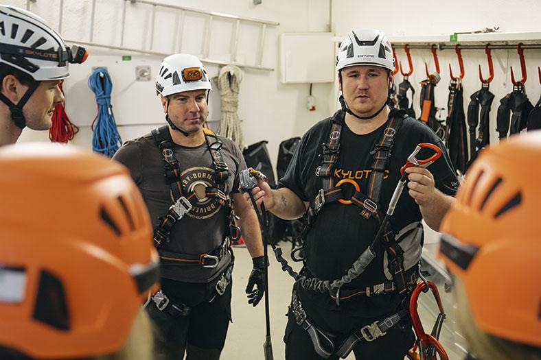 Das Bild zeigt zwei Männer in schwarzen T-Shirts. Sie stehen in einem Raum mit Seilen und Steigschutz-Gegenständen an der Wand. Beide tragen einen weißen Schutzhelm sowie schwarz-orangene Sicherungsgurte um den Oberkörper. Das Mann links hält Seilenden mit Karabinerhaken und Seilführung in die Höhe.