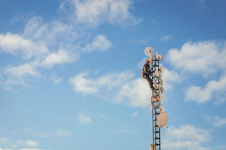 Arbeiter in Schutzausrüstung mit Helm und Gurtsicherung arbeitet an der Spitze eines Antennenträgers mit Satellitenschüsseln, im Hintergrund blauer Himmel mit einigen weißen Wolken.