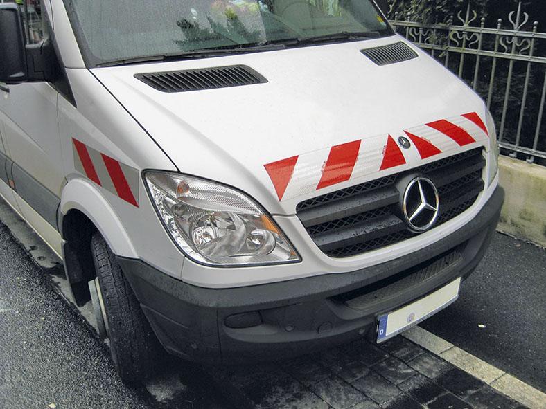 Ausschnitt der Vorderseite eine weißen Mercedes-Transporters mit rot-weißen Warnmarkierungen auf der Motorhaube und am vorderen Kotflügel. Er parkt auf einer Straße neben einem gusseisernen Zaun.
