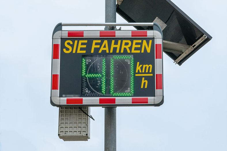 Das Foto zeigt ein solarbetriebene Geschwindigkeitsmass- und Anzeigesystem, das die gefahrene Geschwindigkeit eines sich nähernden Fahrzeugs in grünen Ziffern anzeigt. Die Anzeigetafel hat einen rot-weiß-gestreiften Rand.