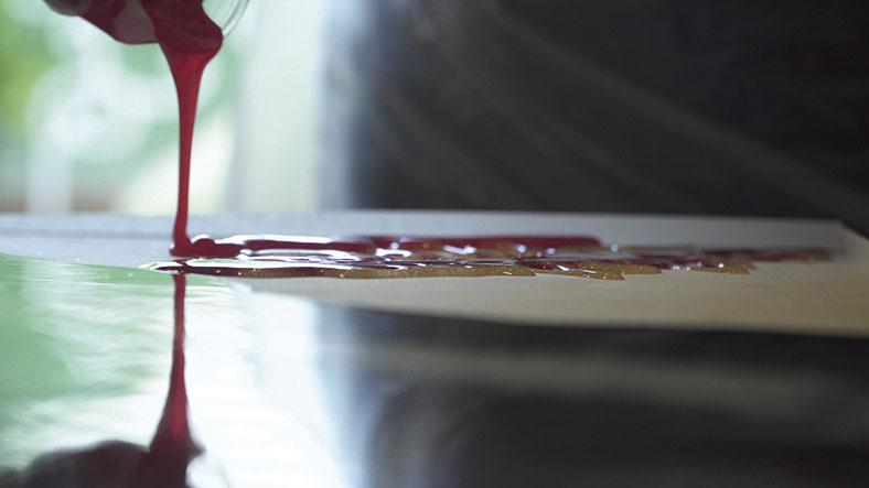 Vom linken oberen Bildrand fließt eine dickflüssige rote Masse auf eine glatte, spiegelnde Oberfläche und mischt sich dort mit einer goldfarbenen Masse.