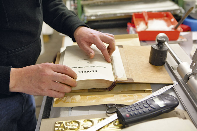 Das Bild zeigt ein aufgeschlagenes, altes Buch, an dem ein Mann in dunklem Pullover arbeitet. Der rechte Buchdeckel ist mit einem Gewicht beschwert, im Hintergrund sieht man einen hellroten Behälter mit weißem Leim.